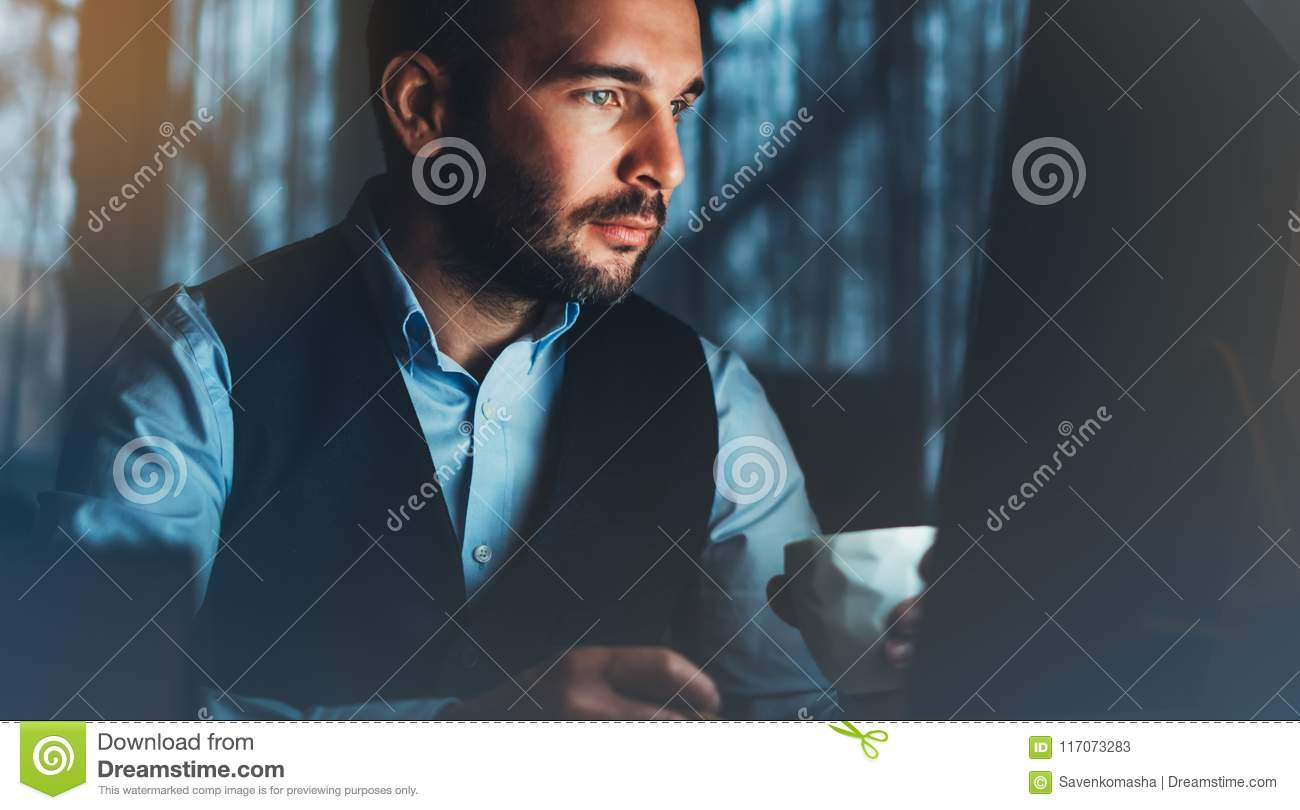 Bearded young businessman working on modern office. Consultant man thinking looking in monitor computer. Manager typing on keyboar