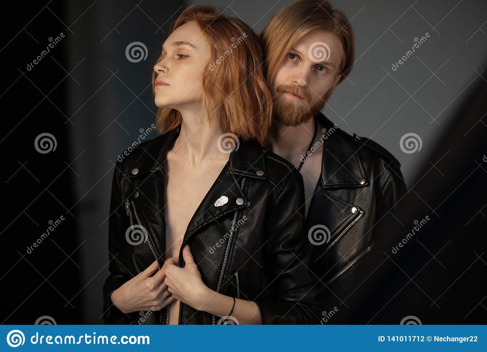 Bearded young man with long brown hair in leather jacket standing behinde his beautiful girlfriend