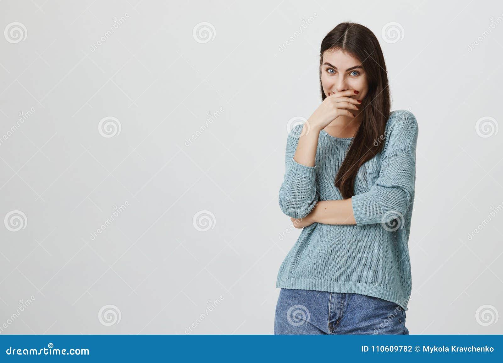Beaturiful e estudante fêmea europeu da proposta, rindo ao cobrir a boca com a mão, estando sobre o fundo cinzento