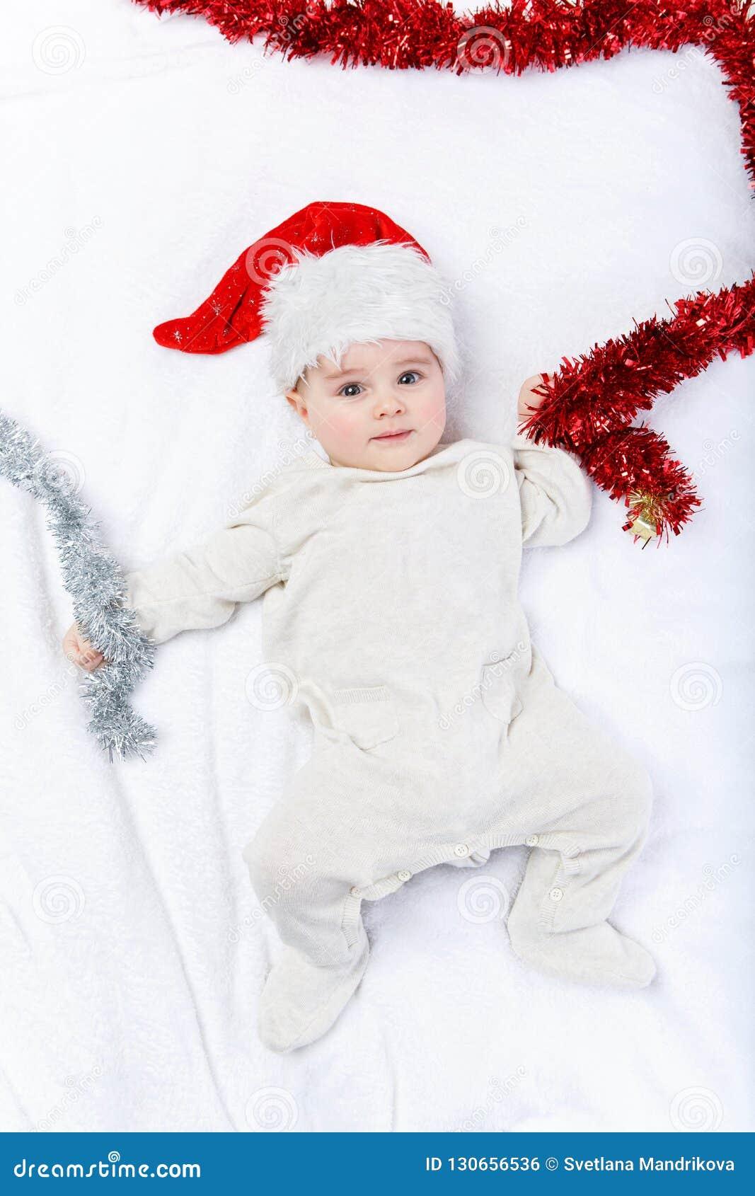e0b7cd9d44f9a Beau bébé garçon dans le bodywear de chapeau et de laine de Noël se  trouvant sur la couverture blanche Projectile de studio Copiez l espace