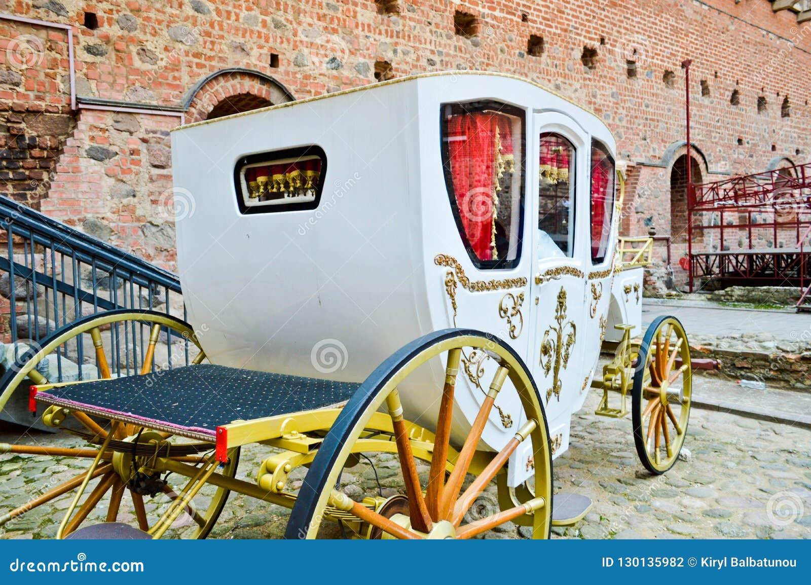 Beau blanc a découpé le chariot riche royal en bois avec de grandes roues décorées des modèles d or à côté du vieil Européen