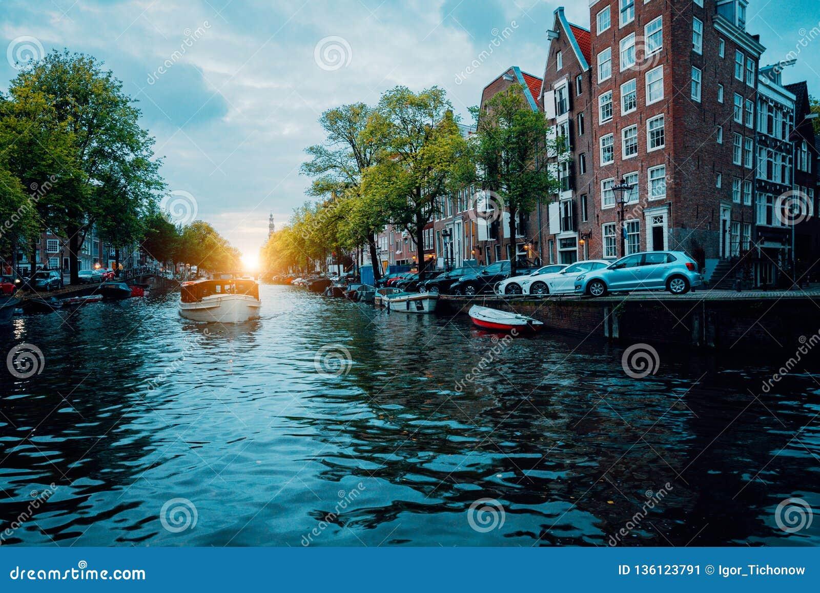 Beau canal bordé d arbres d Amsterdam avec le bateau de croisière dans la lumière chaude de coucher du soleil