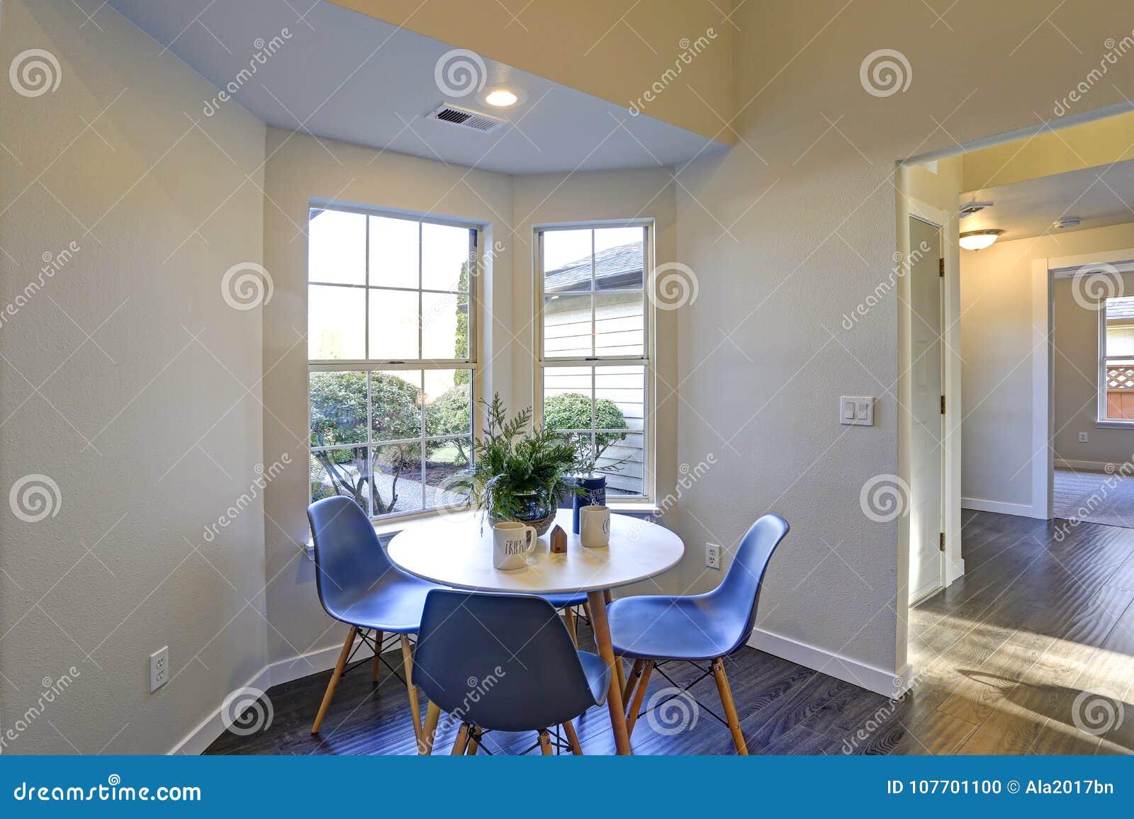 Beau coin-repas avec la table ronde blanche et les chaises bleues