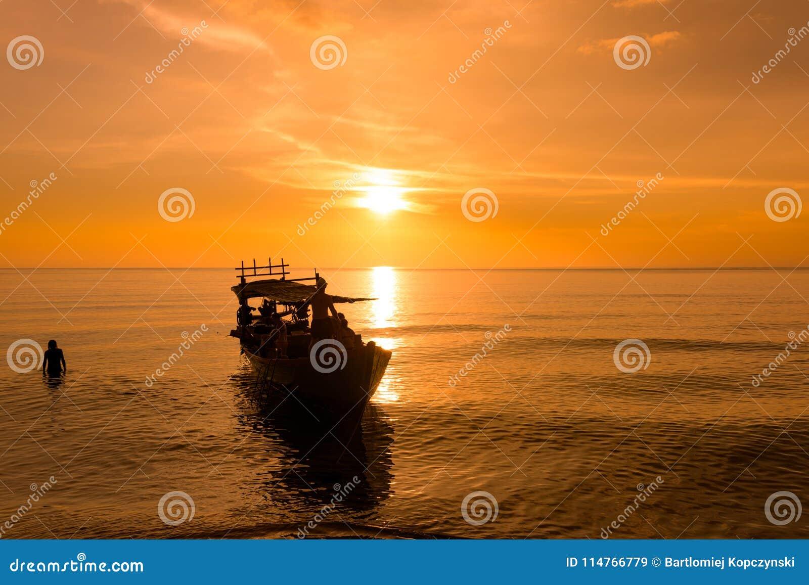 Beau coucher du soleil à la plage de coucher du soleil avec le bateau