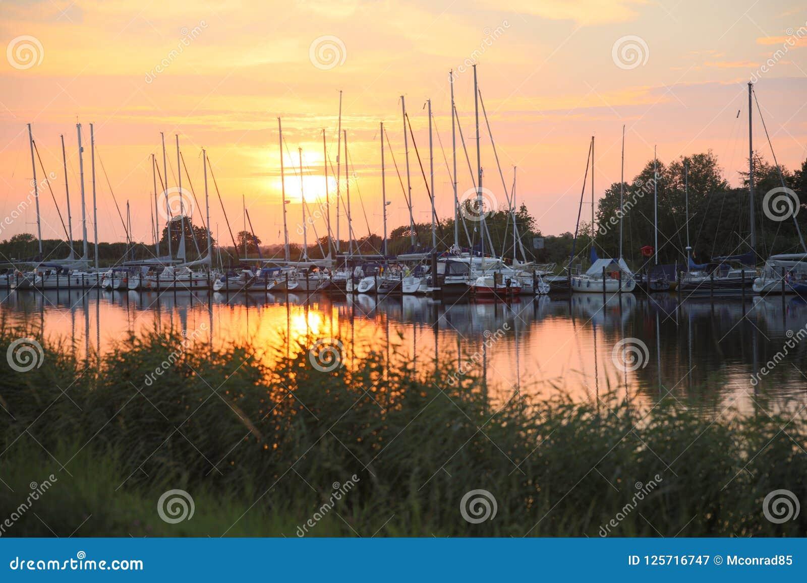 Beau coucher du soleil au-dessus de port de yacht sur la rivière près du greifswald Ger