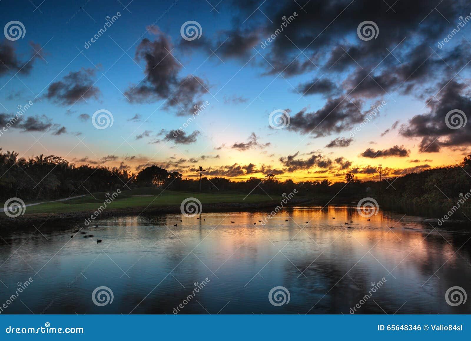 Beau coucher du soleil au-dessus du lac près du terrain de golf dans un tropica