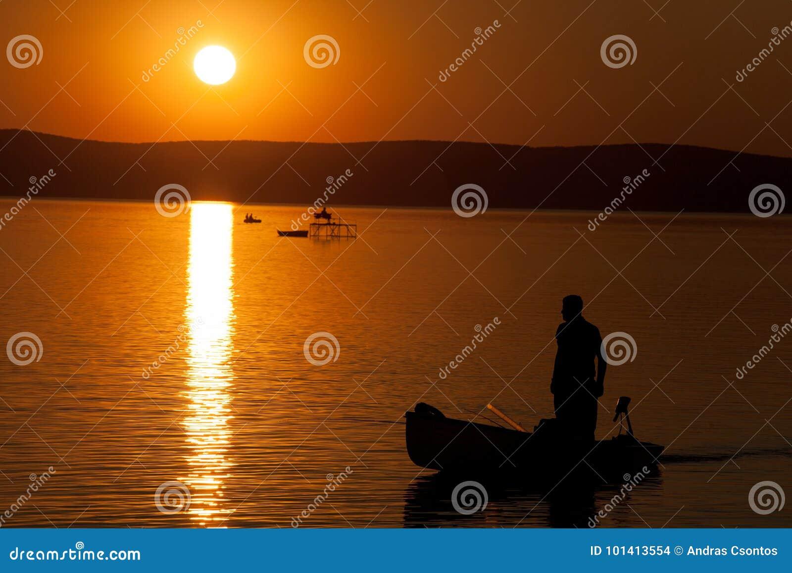 Beau coucher du soleil au-dessus du Lac Balaton avec des silhouettes de ` de pêcheurs à la ligne