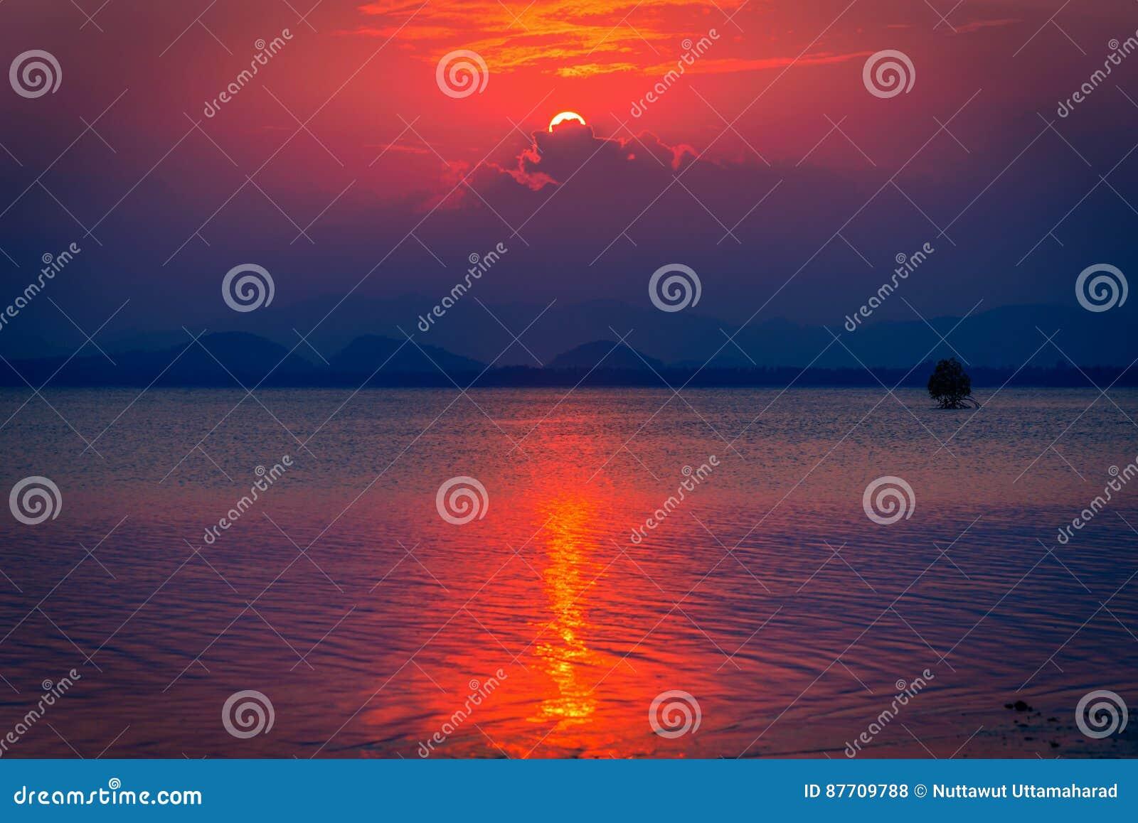 Beau coucher du soleil en ciel gentil au-dessus de mer et de montagnes