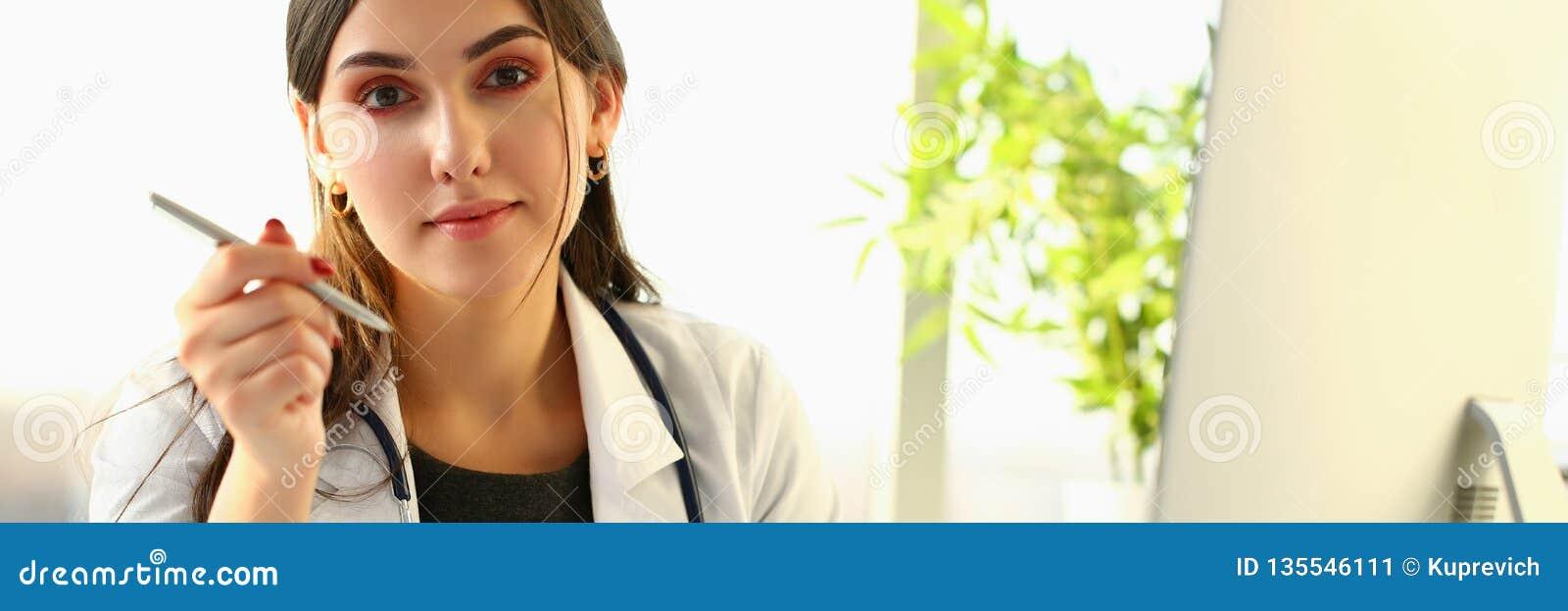Beau docteur féminin de sourire au portrait de lieu de travail