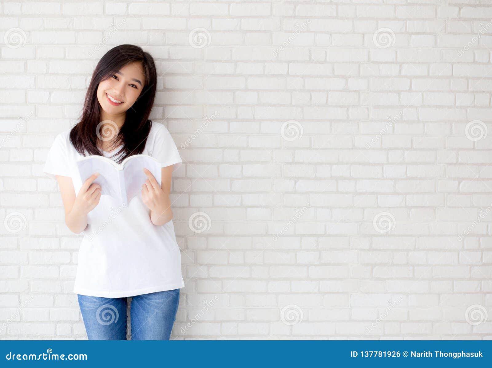 Beau du jeune bonheur asiatique de femme de portrait détendez le livre de lecture debout sur le fond concret de blanc de ciment