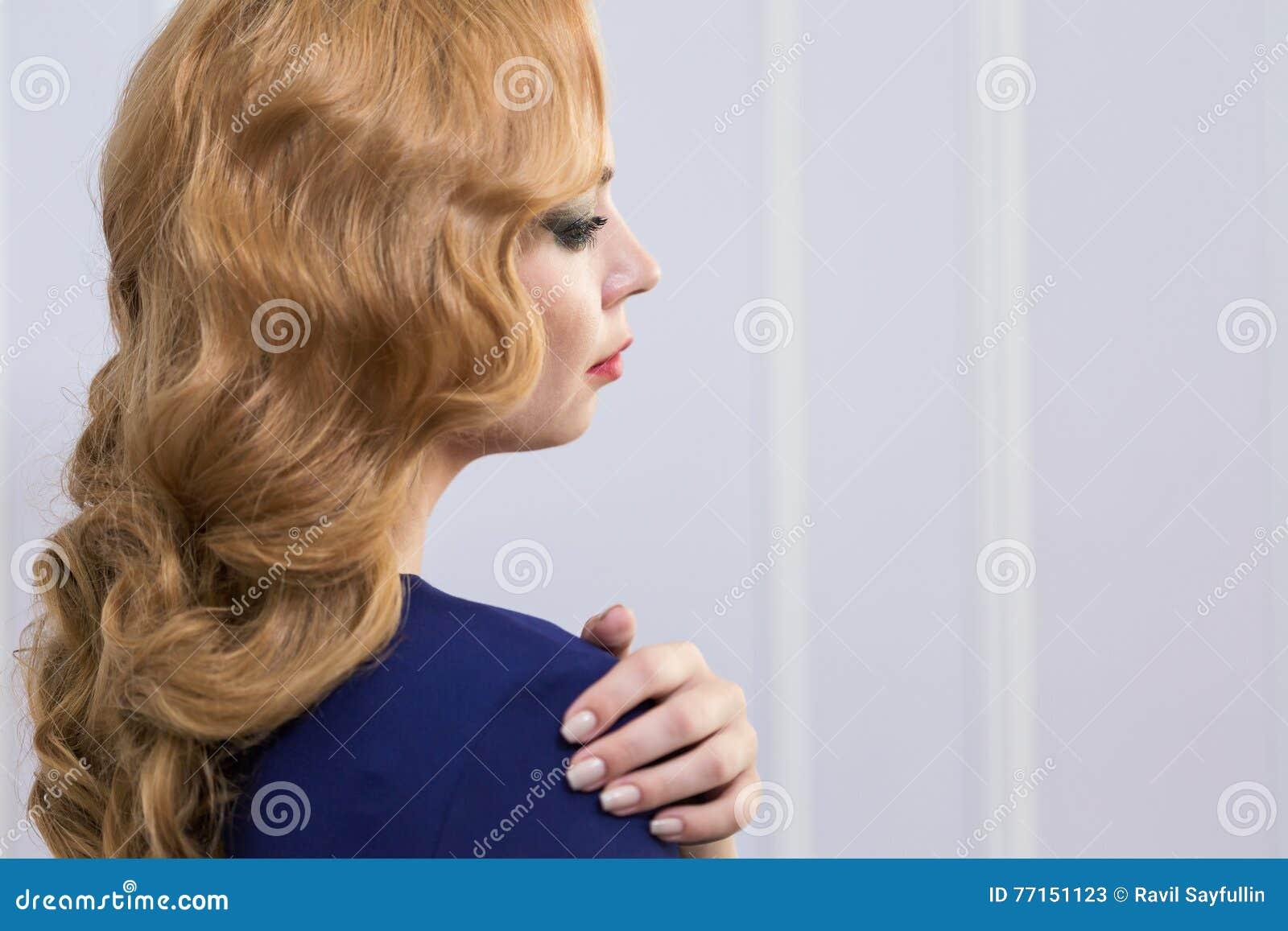 Beau femme avec le long cheveu ondulé Coiffure bouclée et maquillage lumineux faits dans les cheveux et le studio de maquillage