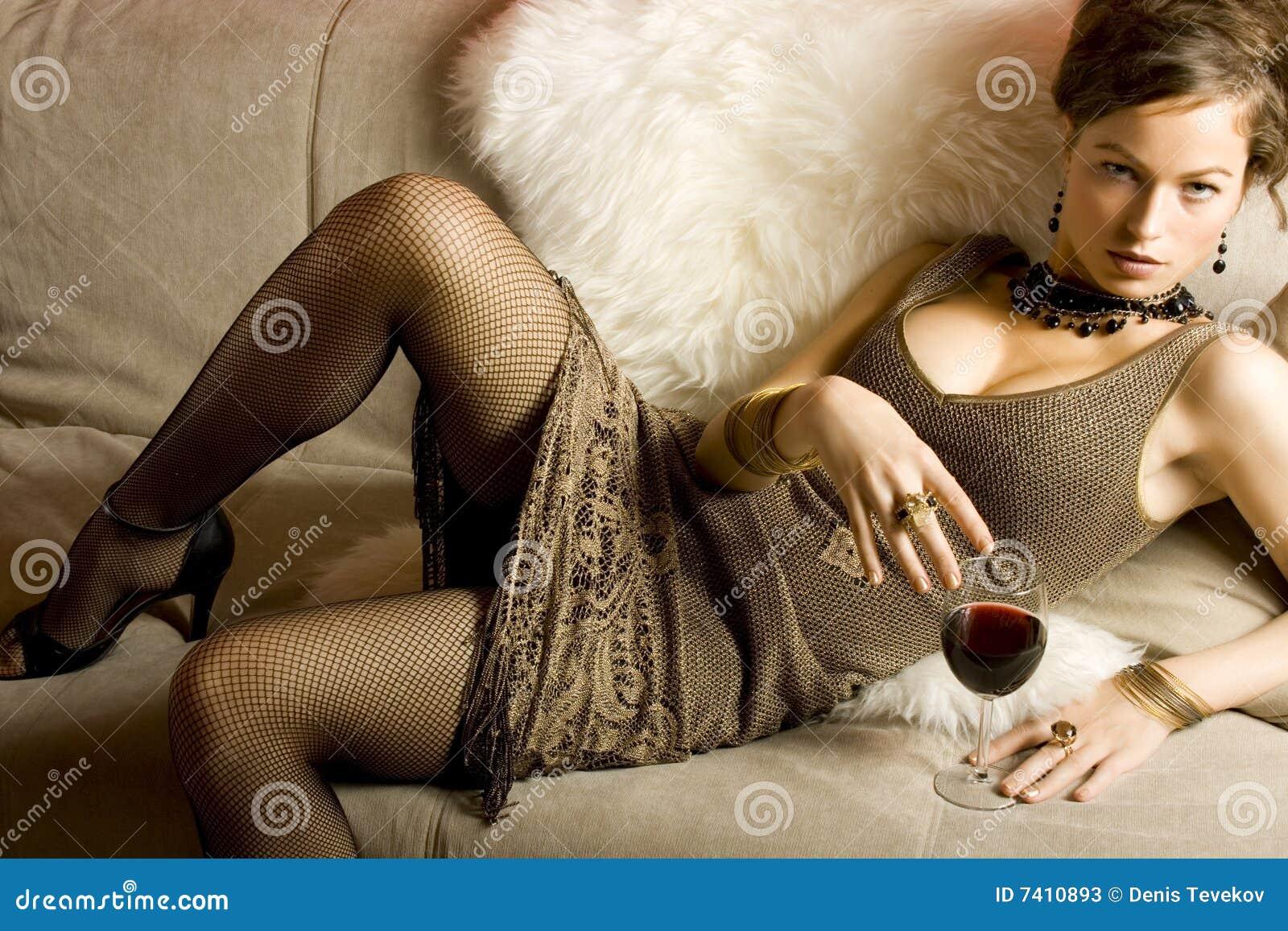Beau femme avec le vin rouge en verre