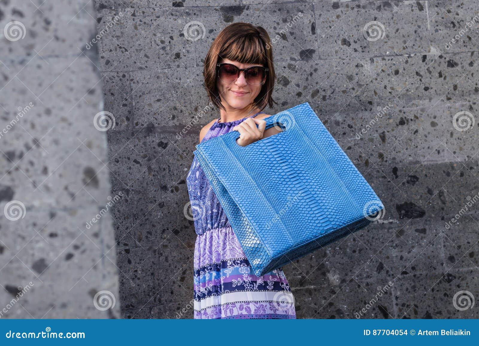 Beau grand sac à main bleu à la mode de python de peau de serpent sur le bras de la fille dans une robe à la mode, posant près du