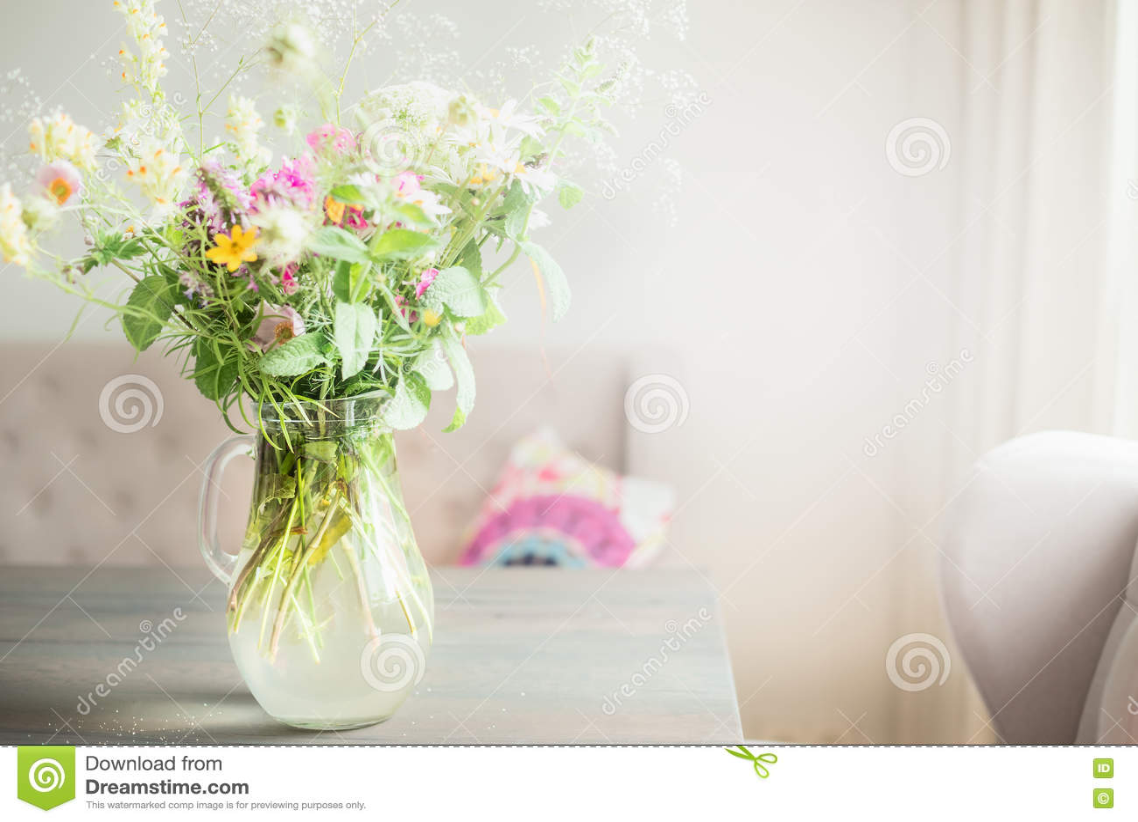 Beau groupe de fleurs sauvages dans le vase en verre sur la table dans le salon léger, décoration à la maison