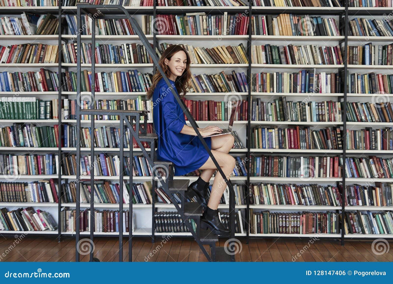 Beau jeune étudiant universitaire s asseyant sur des escaliers dans la bibliothèque, travaillant sur l ordinateur portable