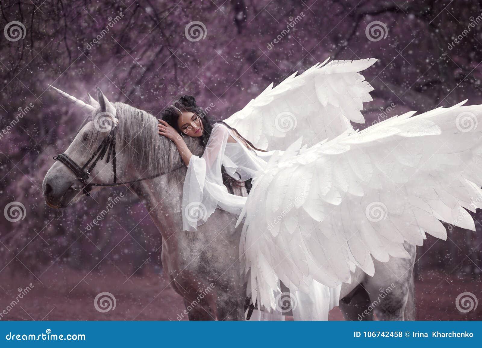 Beau, jeune elfe, marchant avec une licorne Elle porte une lumière incroyable, robe blanche Hotography d art