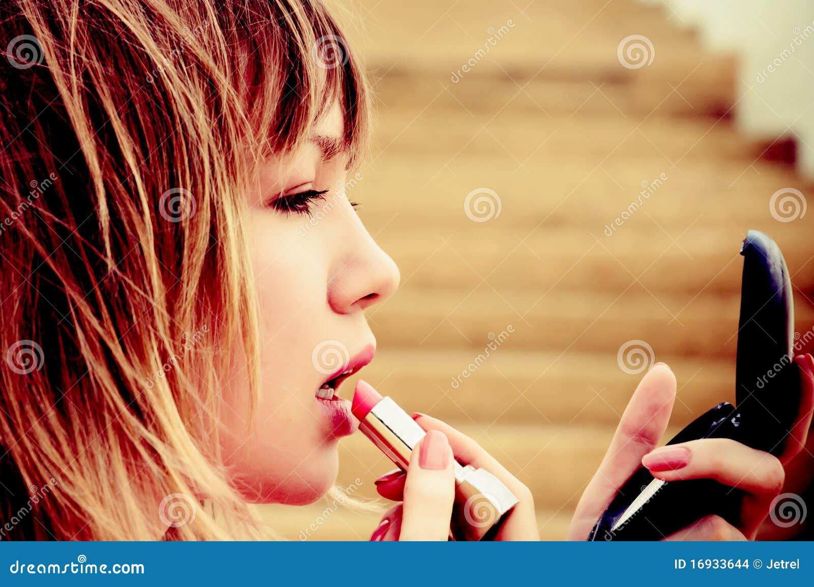 Beau jeune femme avec le rouge à lievres et le miroir