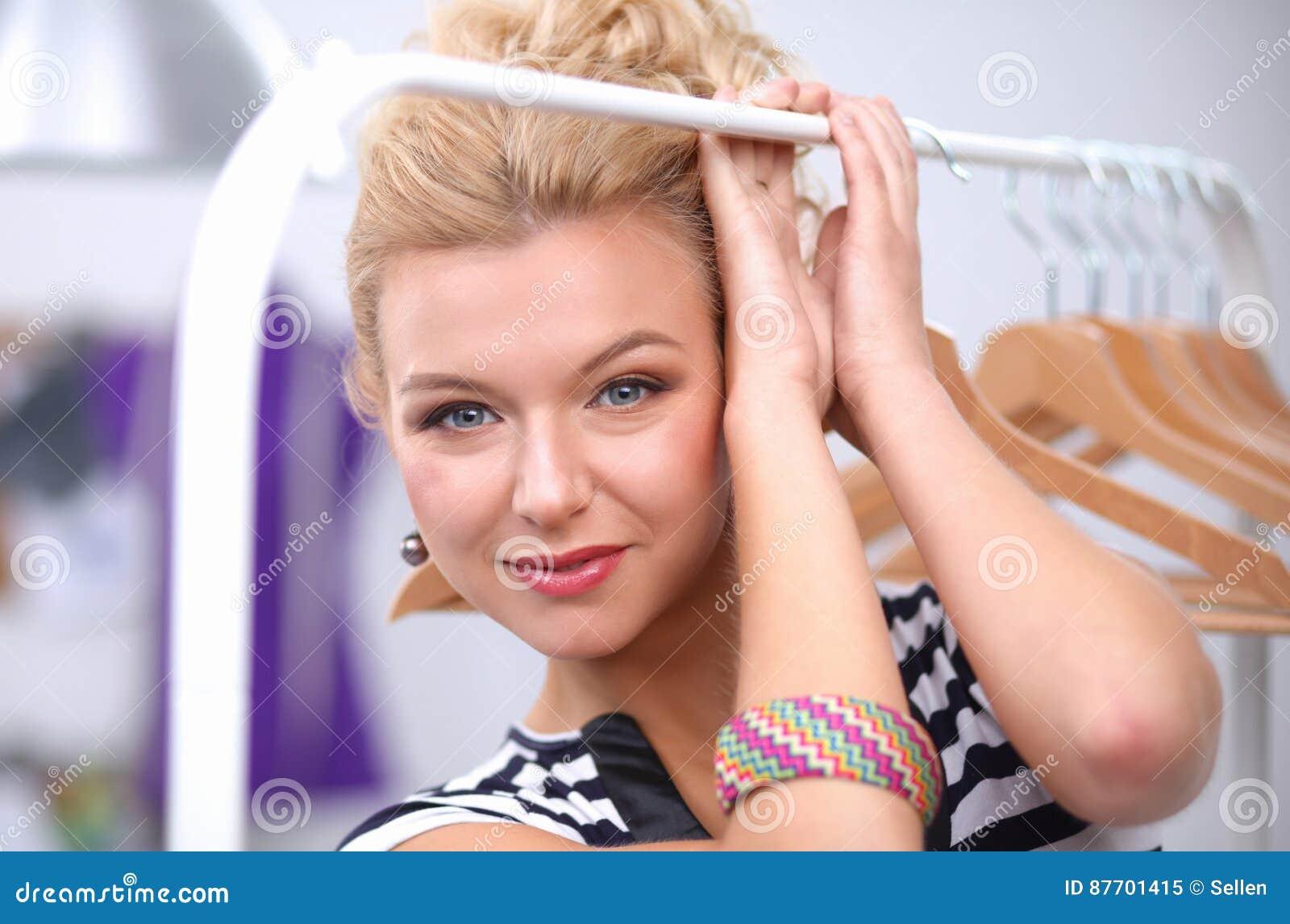 Beau jeune styliste près de support avec des cintres
