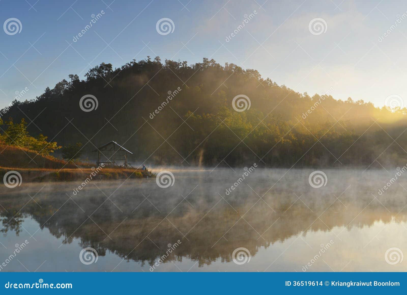 Beau lever de soleil et brume de matin dans le lac.