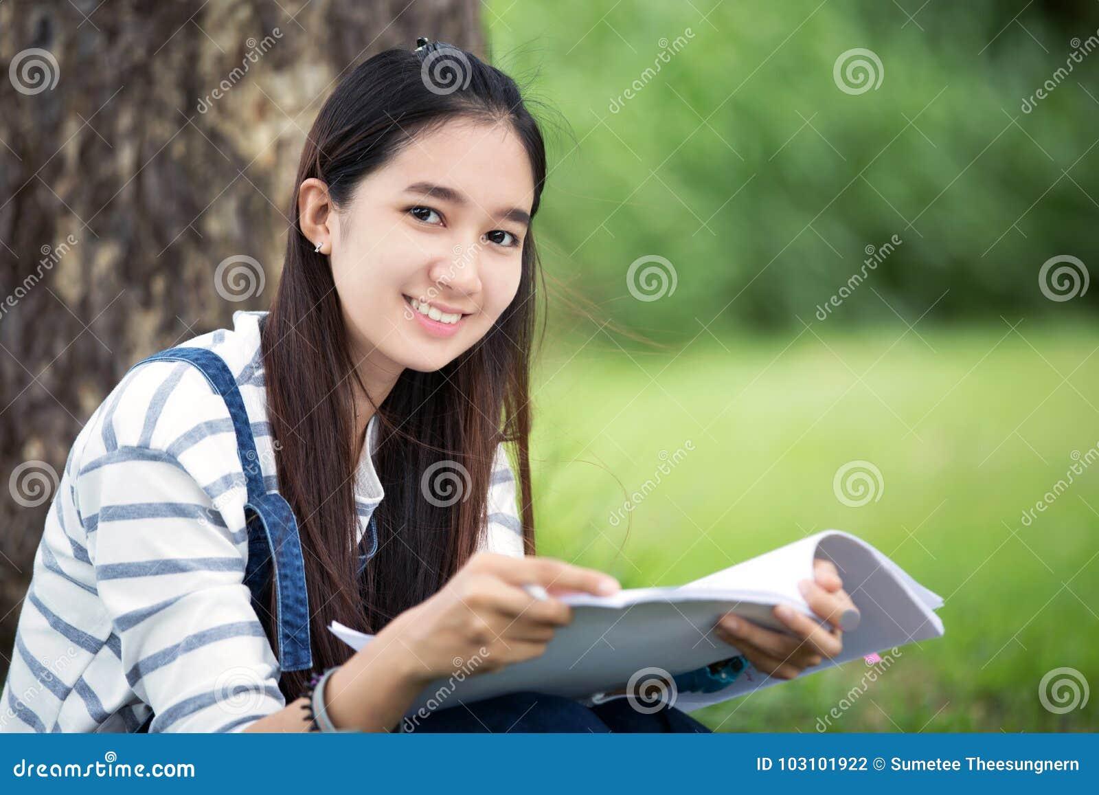 Beau livre et fonctionnement de lecture asiatique de sourire de fille à l arbre dessus