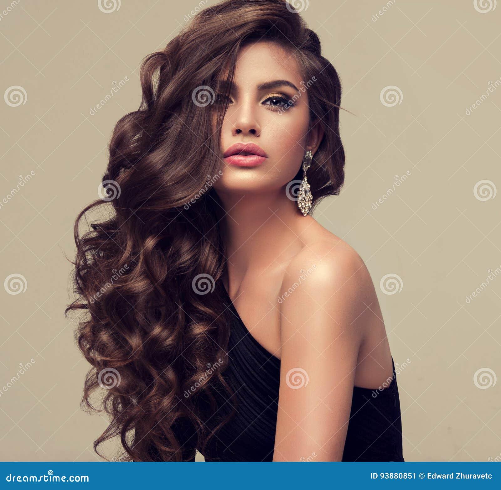 Beau modèle avec longtemps, dense et bouclée la coiffure
