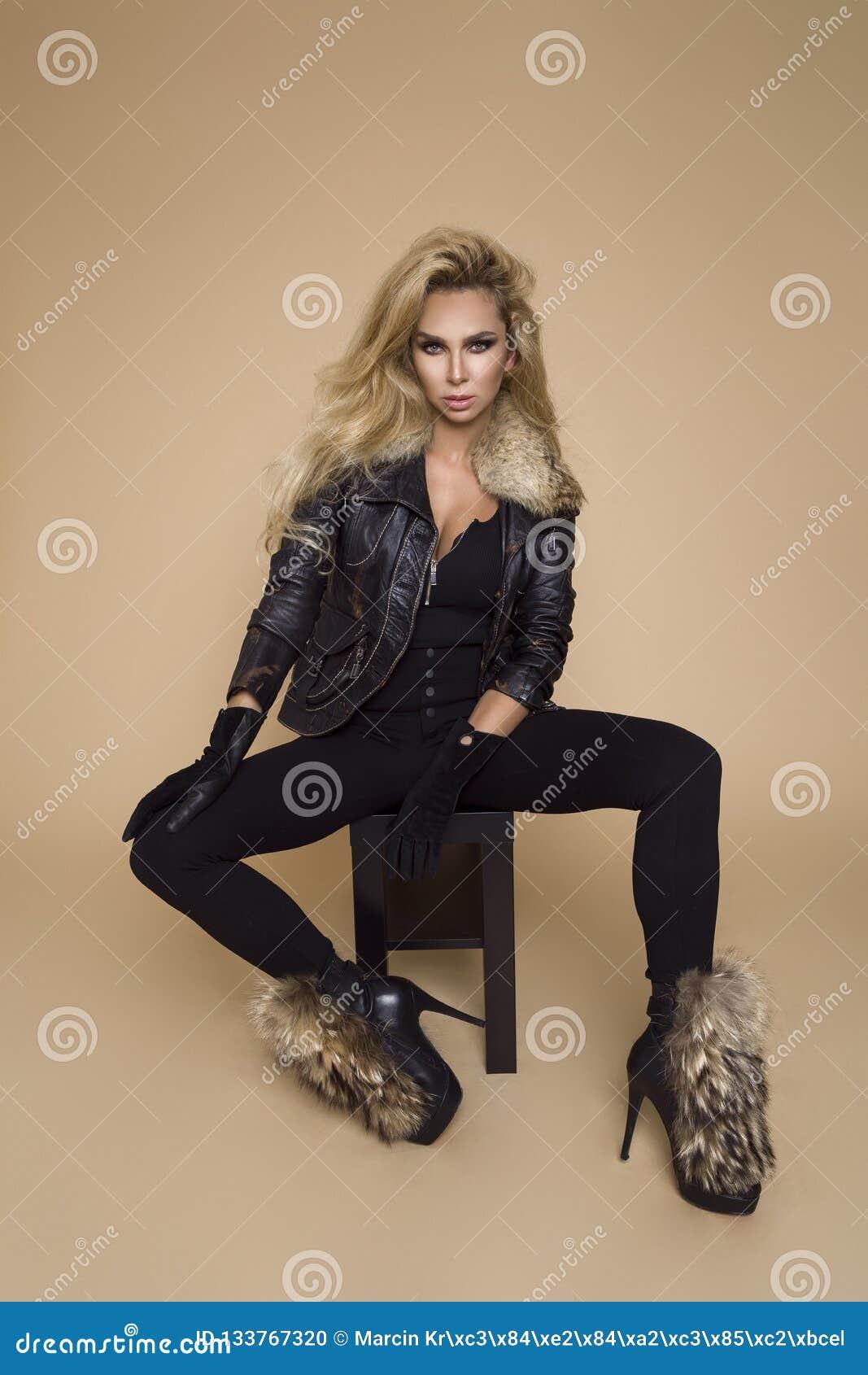 Beau modèle femelle dans un habillement d automne-hiver, une veste en cuir et des bottes sur un fond beige dans le studio Blond d