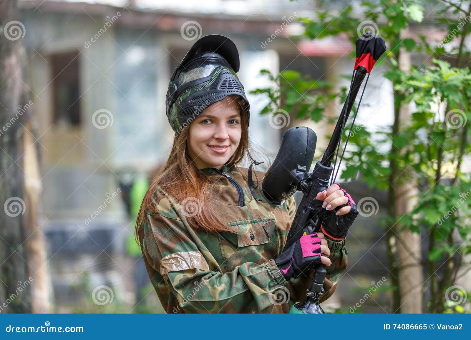 Beau modèle femelle posant dans des munitions de paintball dehors
