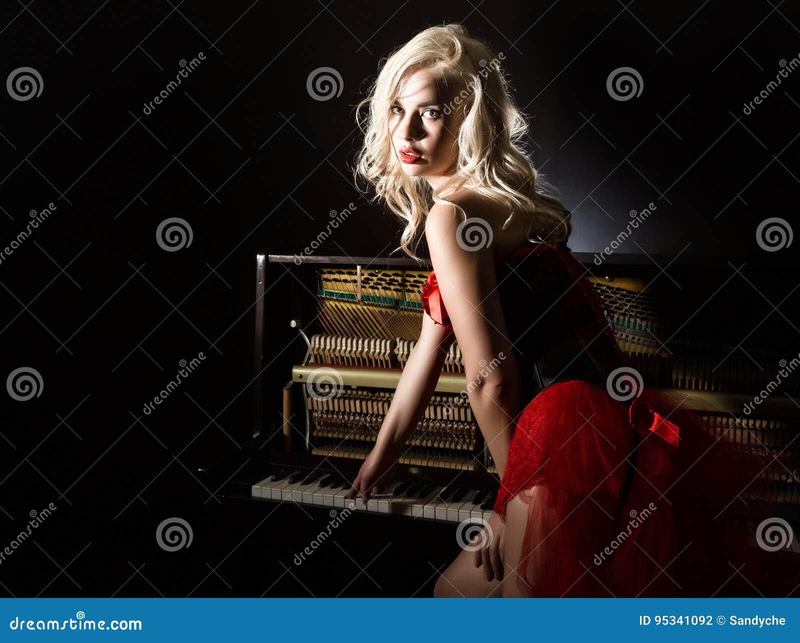 Beau musicien blond dans le corset rouge se tenant près du piano Femme de style de vintage belle