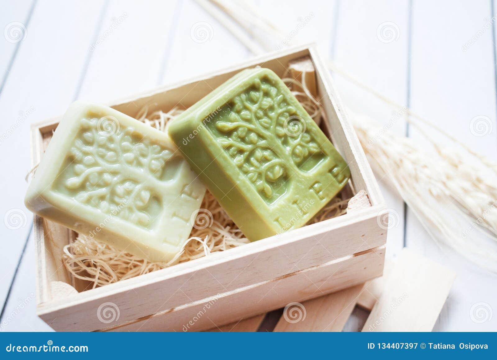 Beau, parfumé savon fait main dans la boîte en bois se tenant sur un fond en bois