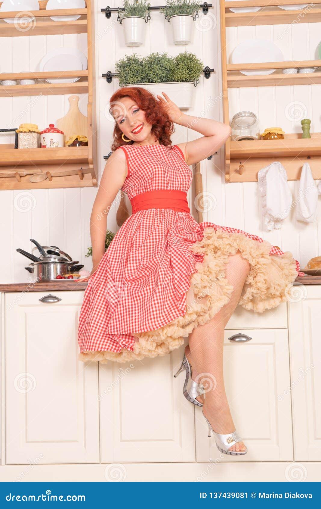 Beau pin-up roux souriant heureusement fille posant dans une rétro robe rouge dans seule la cuisine