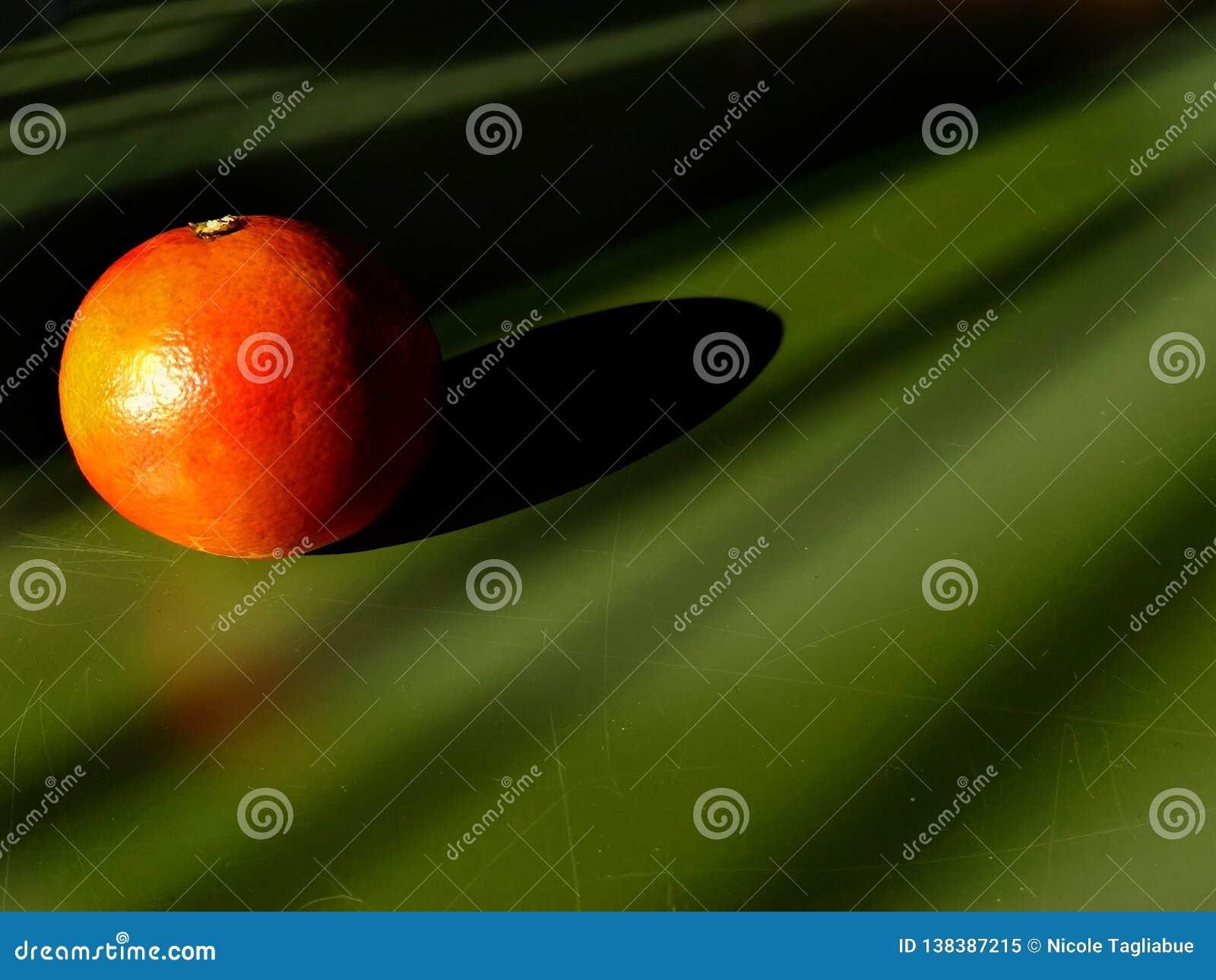 Beau plan rapproché orange de mandarine au soleil léger avec l ombre sur un fond de table verte - concept artistique de fruit
