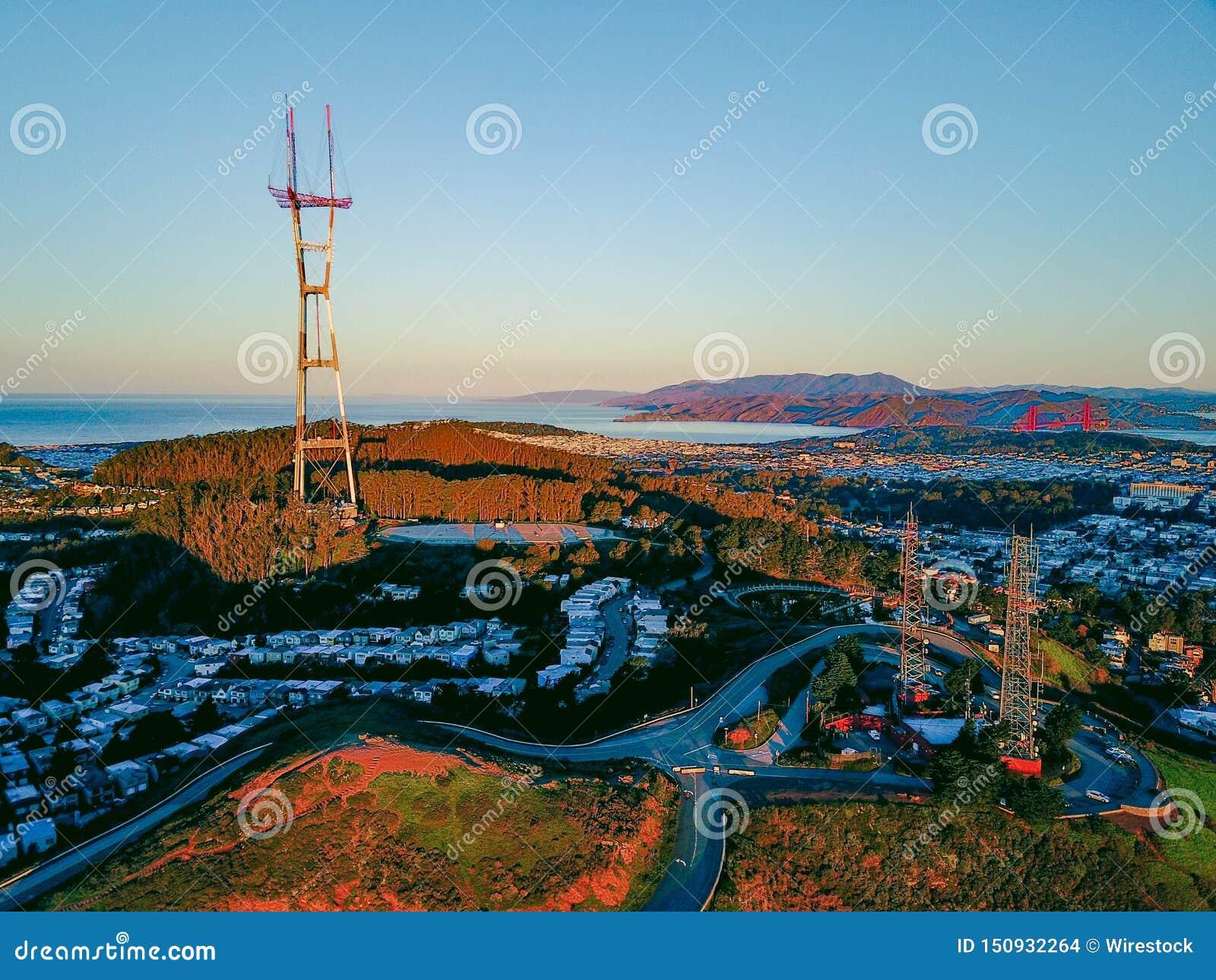 Beau point de repère avec des maisons et une tour de cellules haut en métal sur une colline