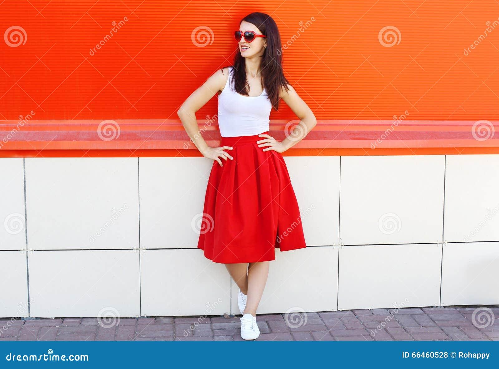 Beau port de femme de brune lunettes de soleil et jupe rouge dans la ville