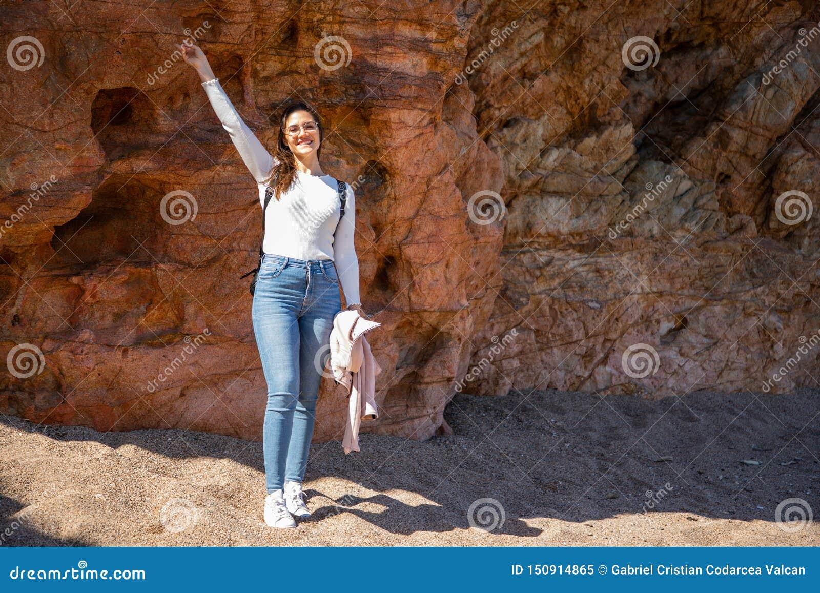 Beau portrait de femme sur les roches de plage pendant le coucher du soleil