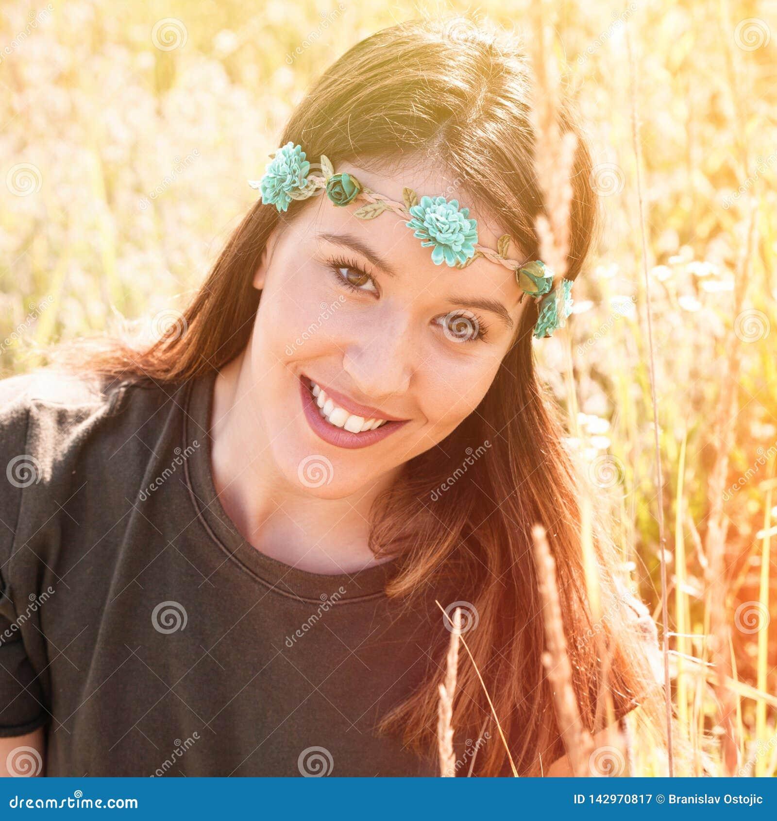 Beau portrait de sourire de boho de jeune femme avec la bande principale avec des fleurs dans le pré d été