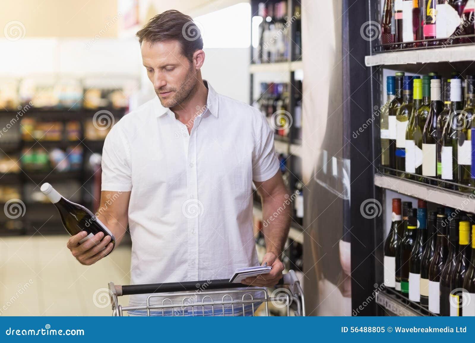 Beau regardant une bouteille de vin ayant dans des ses mains