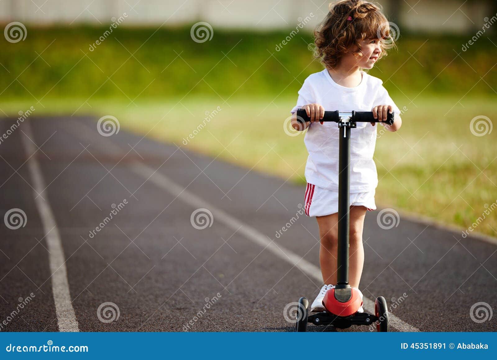 Beau scooter d équitation de fille au stade
