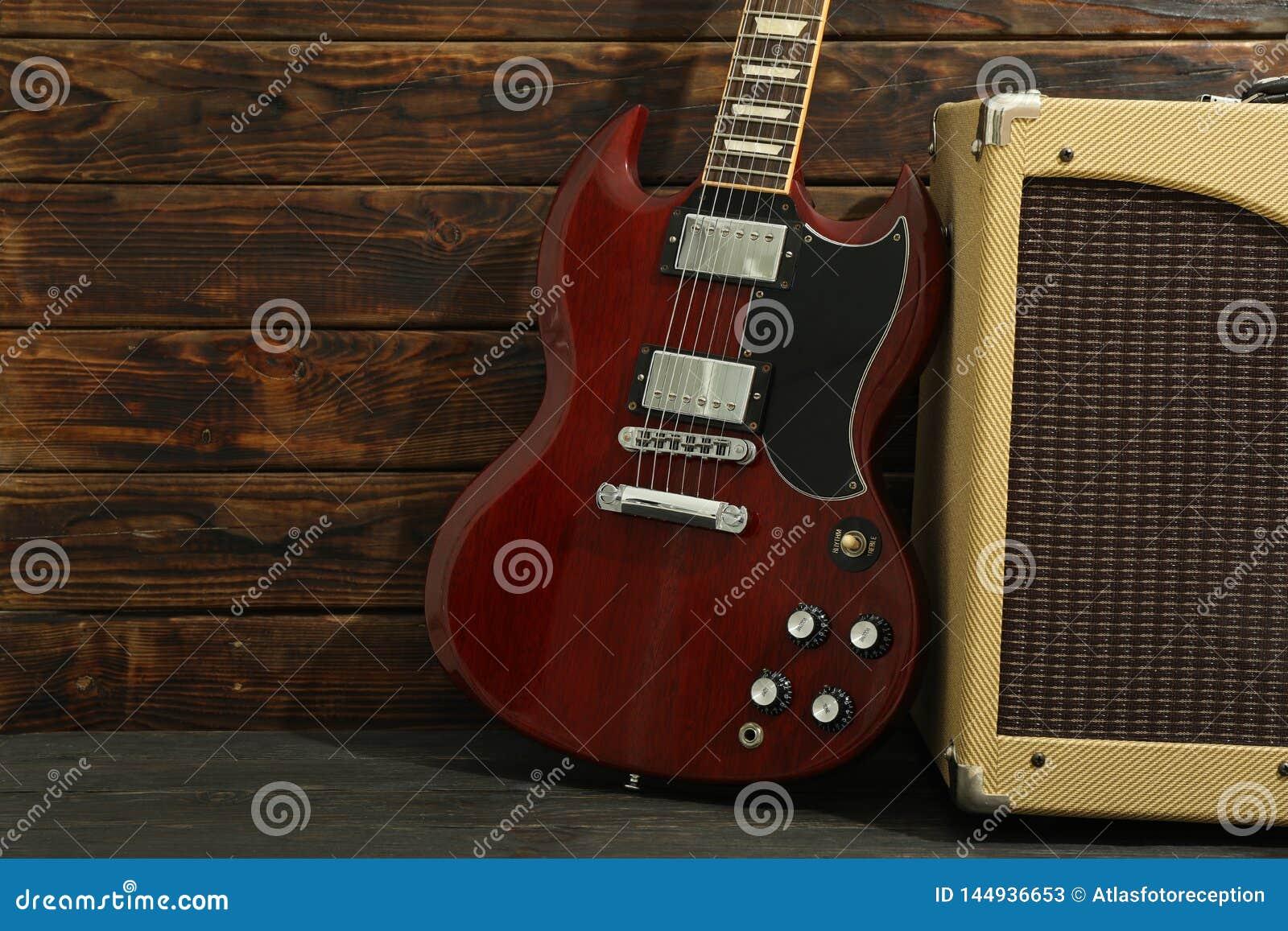 Beau six - guitare électrique de ficelle avec l amplificateur sur le fond en bois