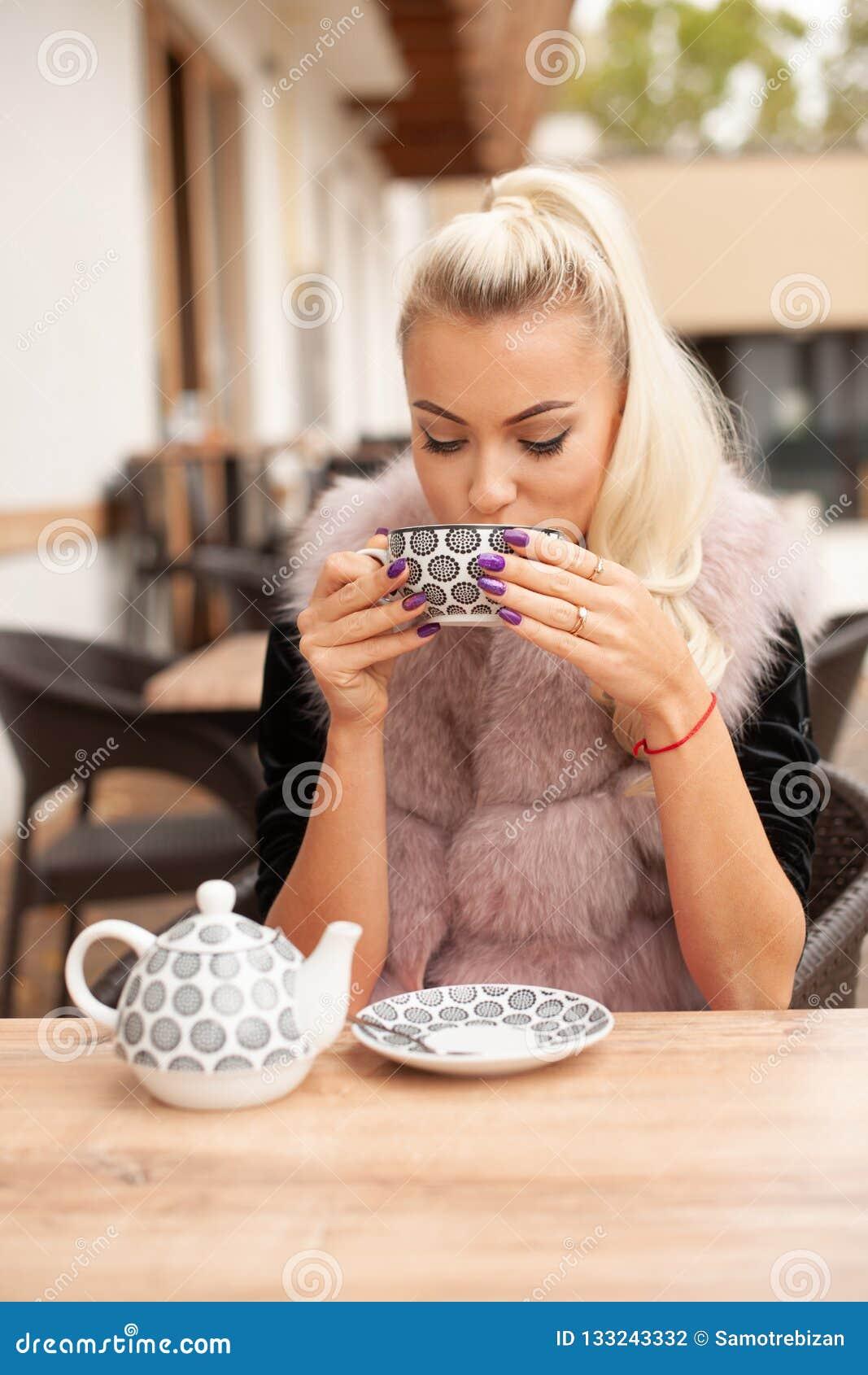 Beau thé de boissons de jeune femme sur le terace de barre en automne tôt