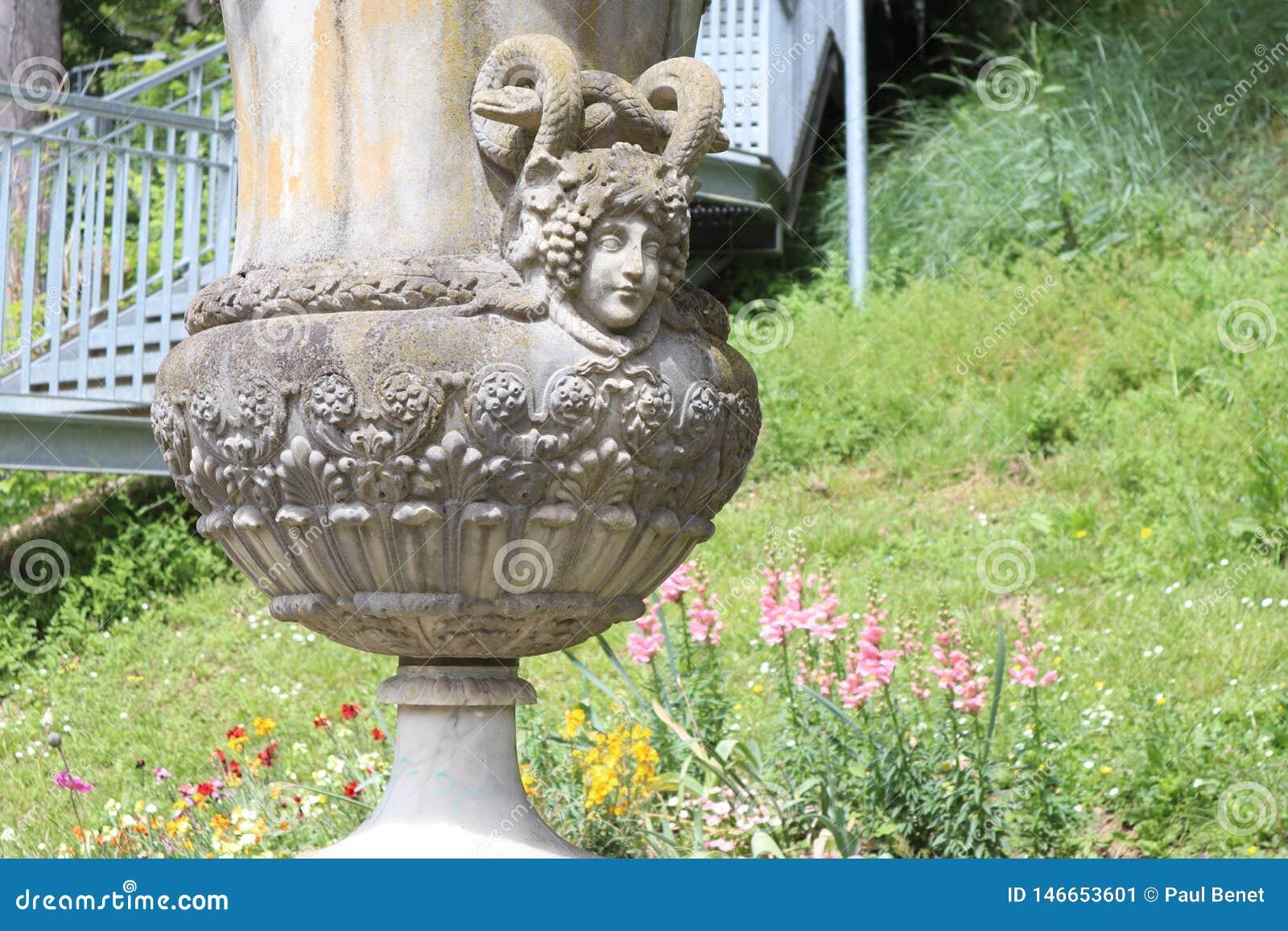 Beau vase antic avec le visage de femmes dans le jardin