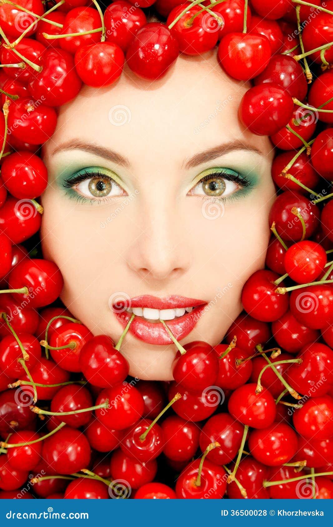 Beau visage de femme avec la grande cerise fraîche mûre rouge