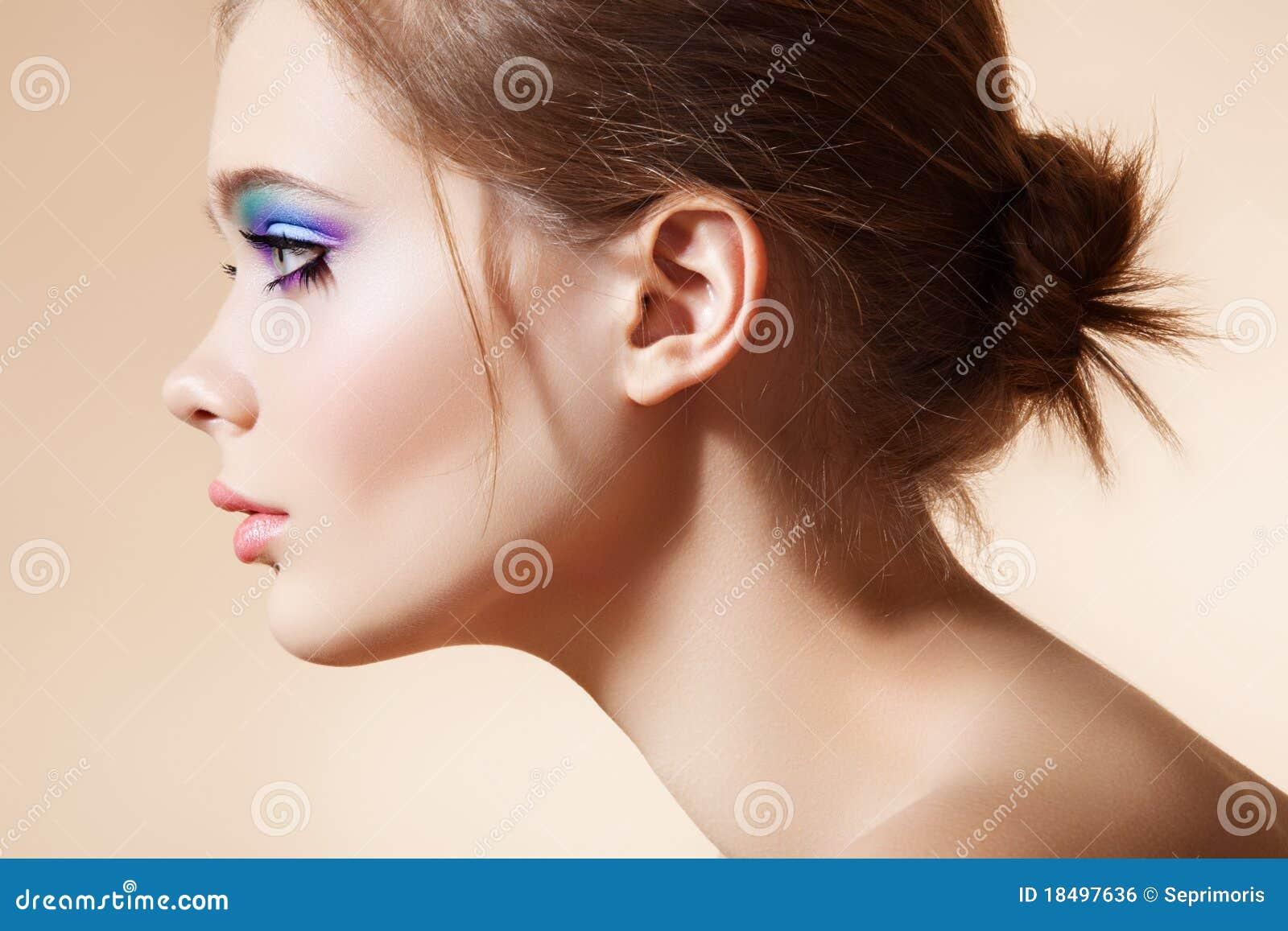 Beau visage de profil avec le renivellement lumineux de mode