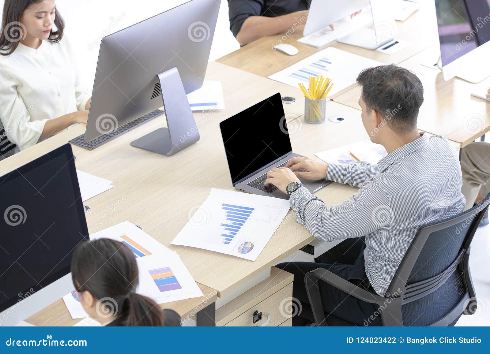 Beaucoup d employés asiatiques sont attentifs sur travailler avec les ordinateurs modernes