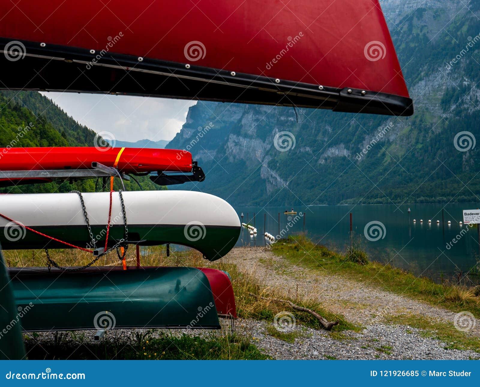 Beaucoup de canoës colorés stockés à un endroit de location à un lac suisse de montagne