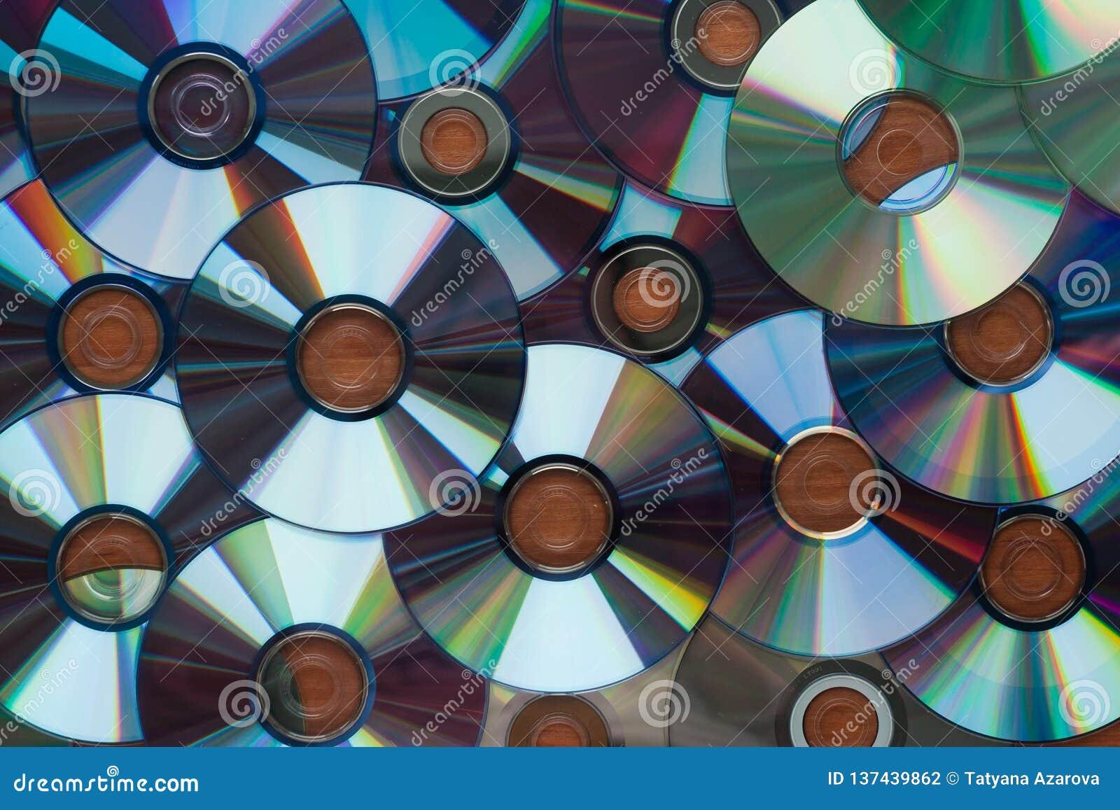 Beaucoup de disques de Cd d ordinateur réfléchissant sur une surface en bois, fond, texture