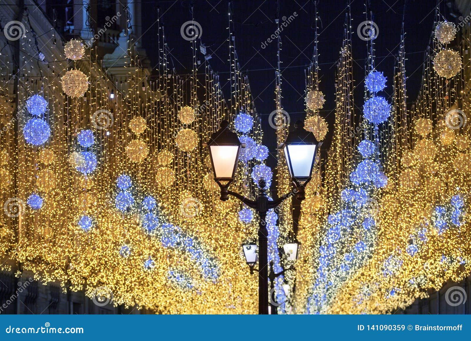 Beaucoup de lumières brûlantes lumineuses bleues et lanternes jaunes accrochant sur le plan rapproché noir de fond de ciel noctur