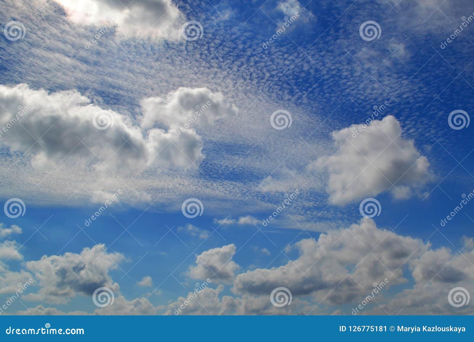 Beaucoup de nuages blancs de différents types : le cumulus, cirrus, a posé haut en ciel bleu