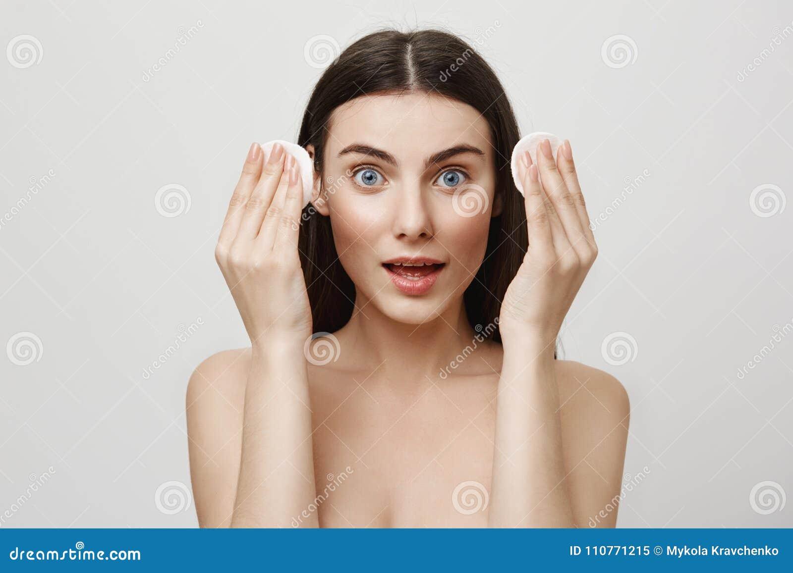 Beauté et concept cosmetological de procédure Portrait de la femme expressive belle tenant des protections de coton dans des main