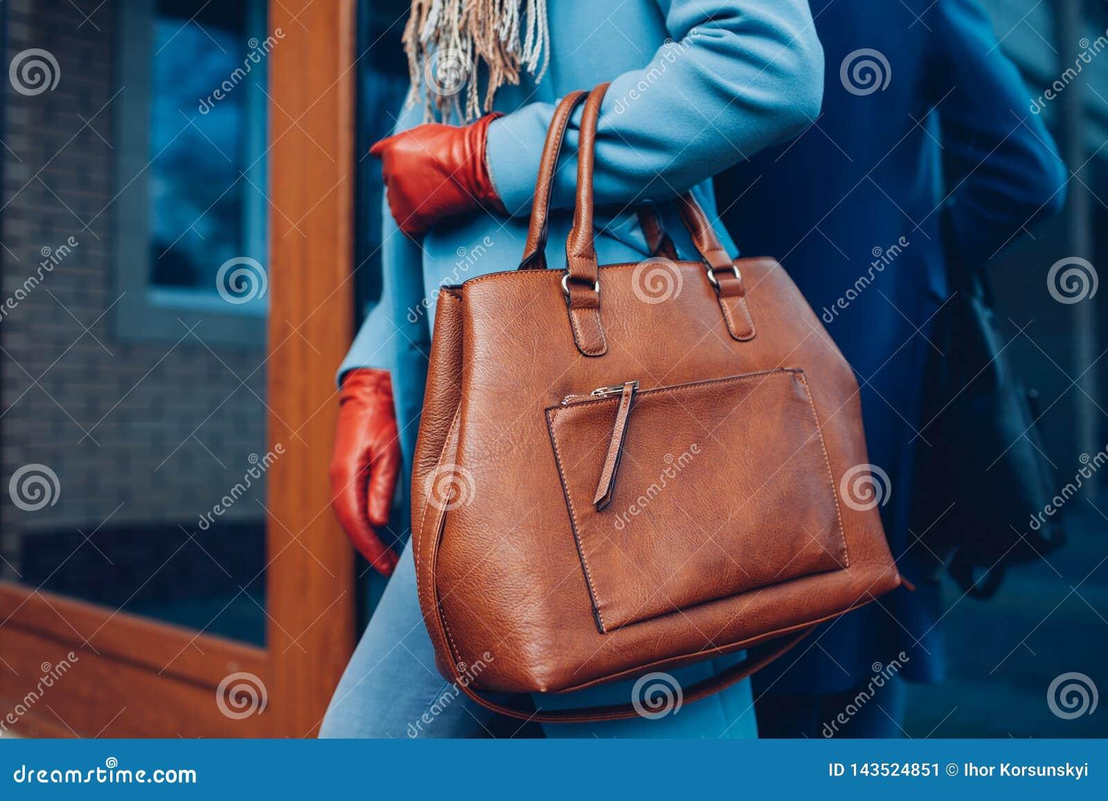 Beauté et mode Manteau de port élégant et gants de femme à la mode, tenant le sac à main brun de sac