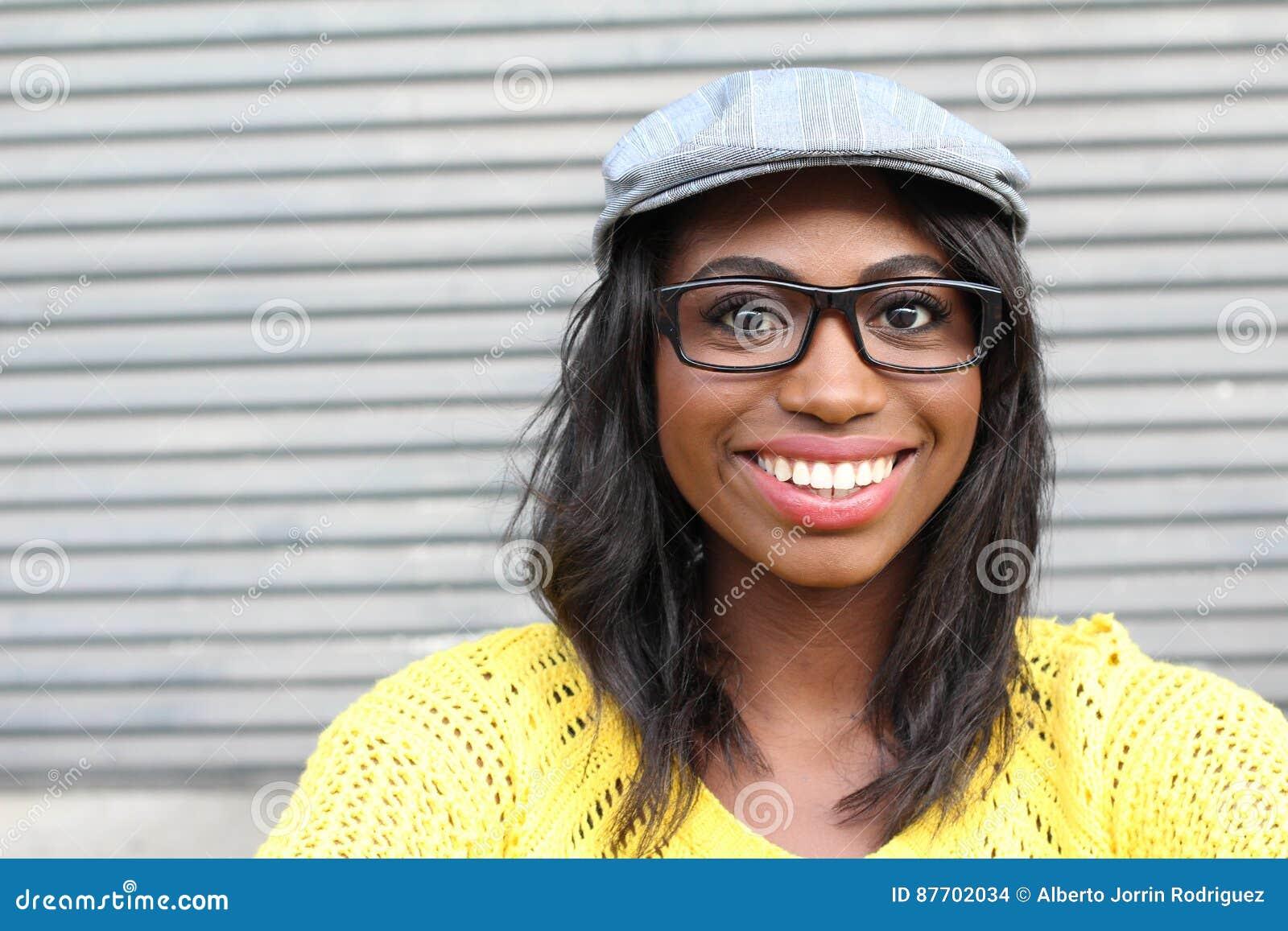 Beauté géniale de style Portrait de la belle jeune femme africaine dans les verres et le chapeau génial souriant tout en se tenan